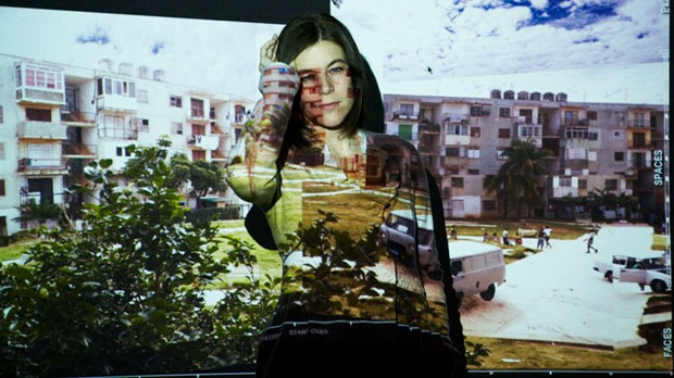 Katerina Cizek covering a part of her face posing in front of a screen projector