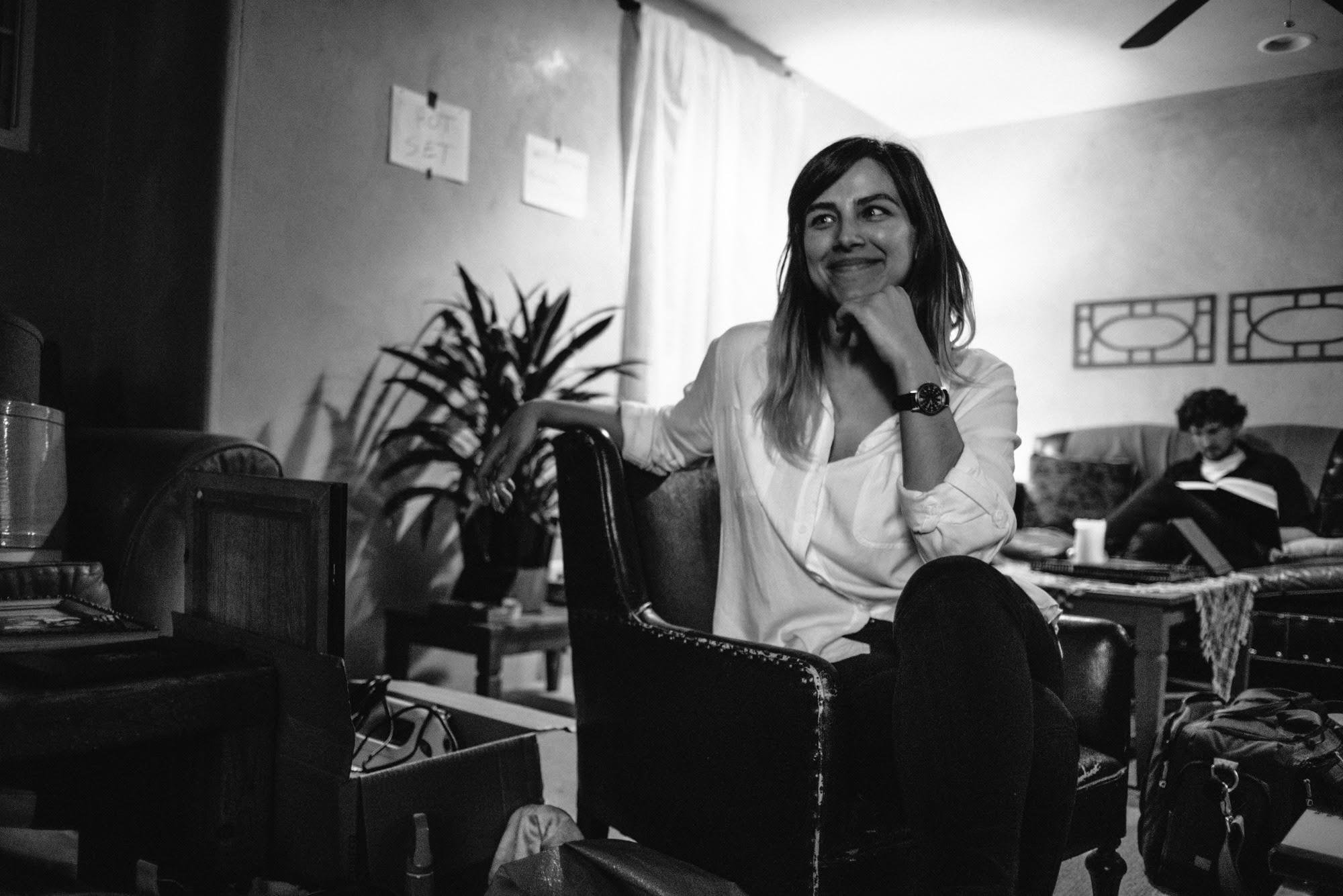 Natasha Kermani sitting and smiling at the set of Imitation Girl
