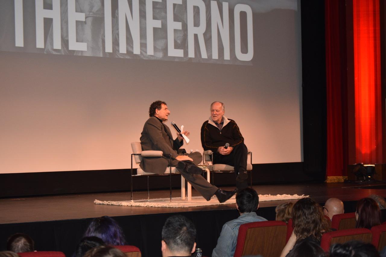 Werner Herzog talking with Professor Herbert Gelder on the podium.