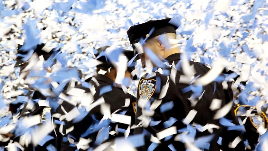 NYPD officers are covered in confetti at a police academy graduation in the documentary Crime + Punishment.