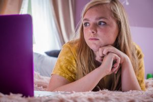 Elsie Fisher as Kaylie in the movie Eigth Grade laying on her bed looking at her computer.