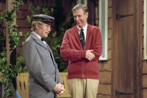 Fred Rogers and David Newell, as Speedy Delivery's Mr. McFeely, stand on the front porch set while filming an episode of Mister Rogers' Neighborhood.