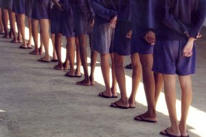 A still from the Maria Ramos documentary Behave that shows minors standing in a line from behind at a juvenile detention facility where you can just see their torsos, legs, and feet in matching blue shorts and sandals.