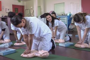 A still from the documentary Each and Every Moment where nursing students are kneeling in lines practicing CPR together.