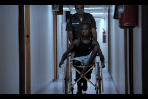 A police officer wheels a disabled man in a wheelchair to his court date in the Maria Ramos documentary Justice.