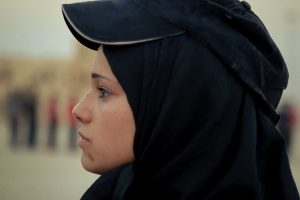 A still from the documentary What Walaa Wants, which is a close up of her face of her wearing a hijab and a hat looking toward the left paying attention to someone offscreen.