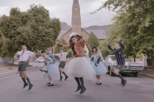A dance scene from the film Kanarie where Schalk Bezuidenhout is dressed in a wedding dress leading a line of dancers in the street.