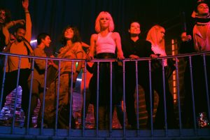 Vanessa Paradis stands with other women at a railing at a nightclub surveying the ground below in the film Knife+Heart.