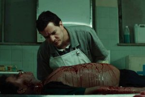 Actor Daniel de Oliveira looks at a corpse in the film The Nightshifter