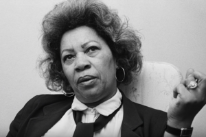A black and white photo of Toni Morrison from when she was editor at Random House looking sideways at the camera and holding up her clenched fist