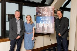 Martin Bright, Katharine Gun, and Gavin Hood stand by a poster for the film Official Secrets