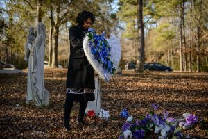 Claudia Lacy at her son Lennon's grave with a heart on a stand made of blue and white flowers