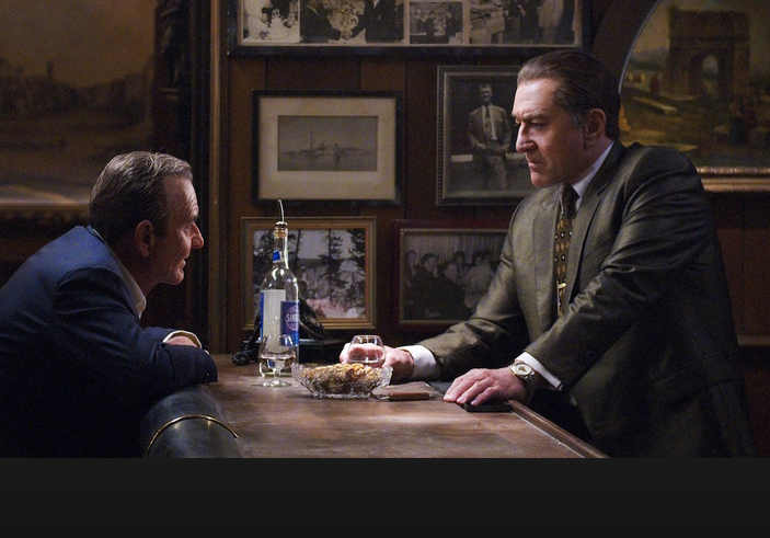 Joe Pesci and Robert De Niro leaning across a table to talk to each other in the movie The Irishman
