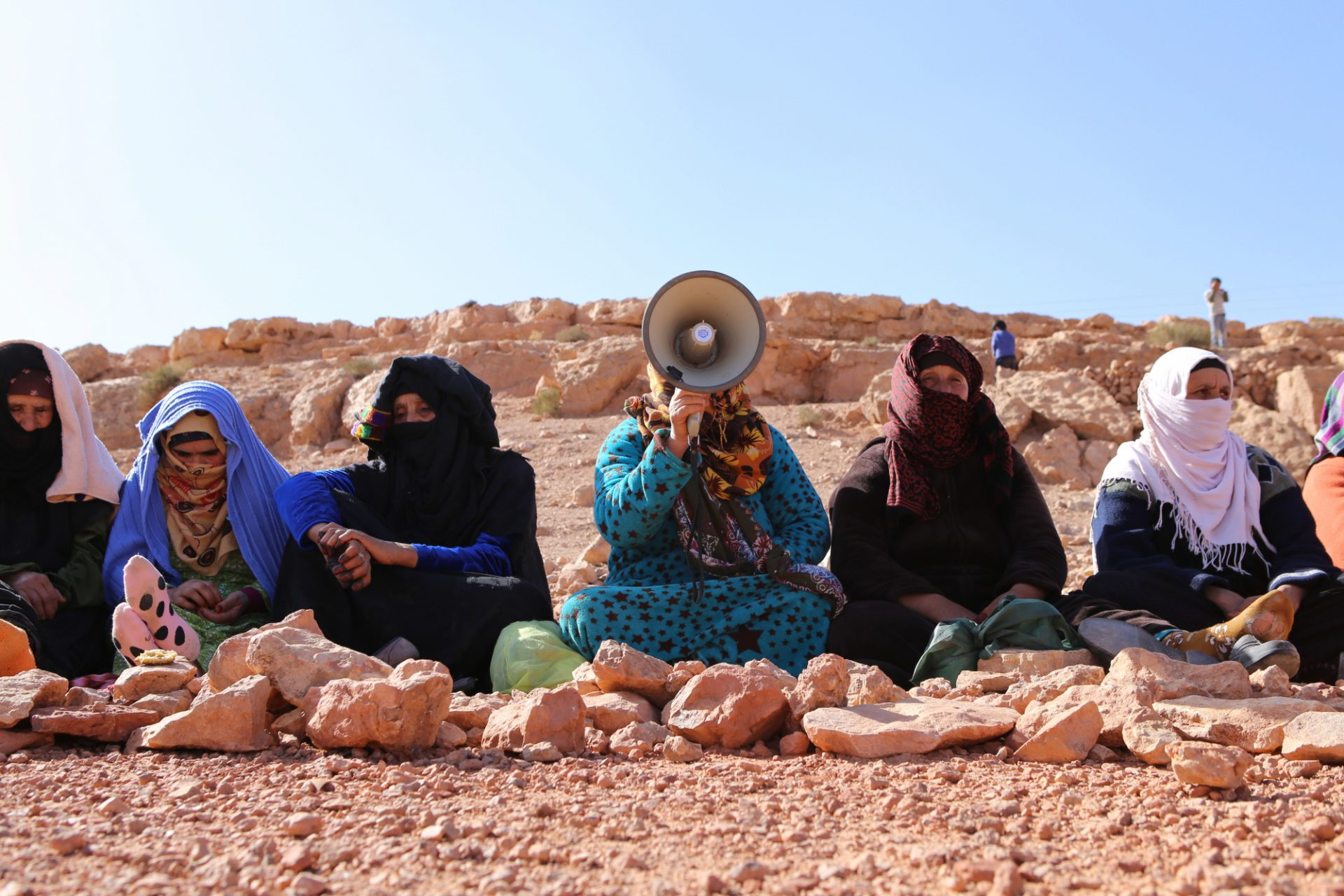 Moroccan women sit in a line while one woman with a megaphone leads a protest