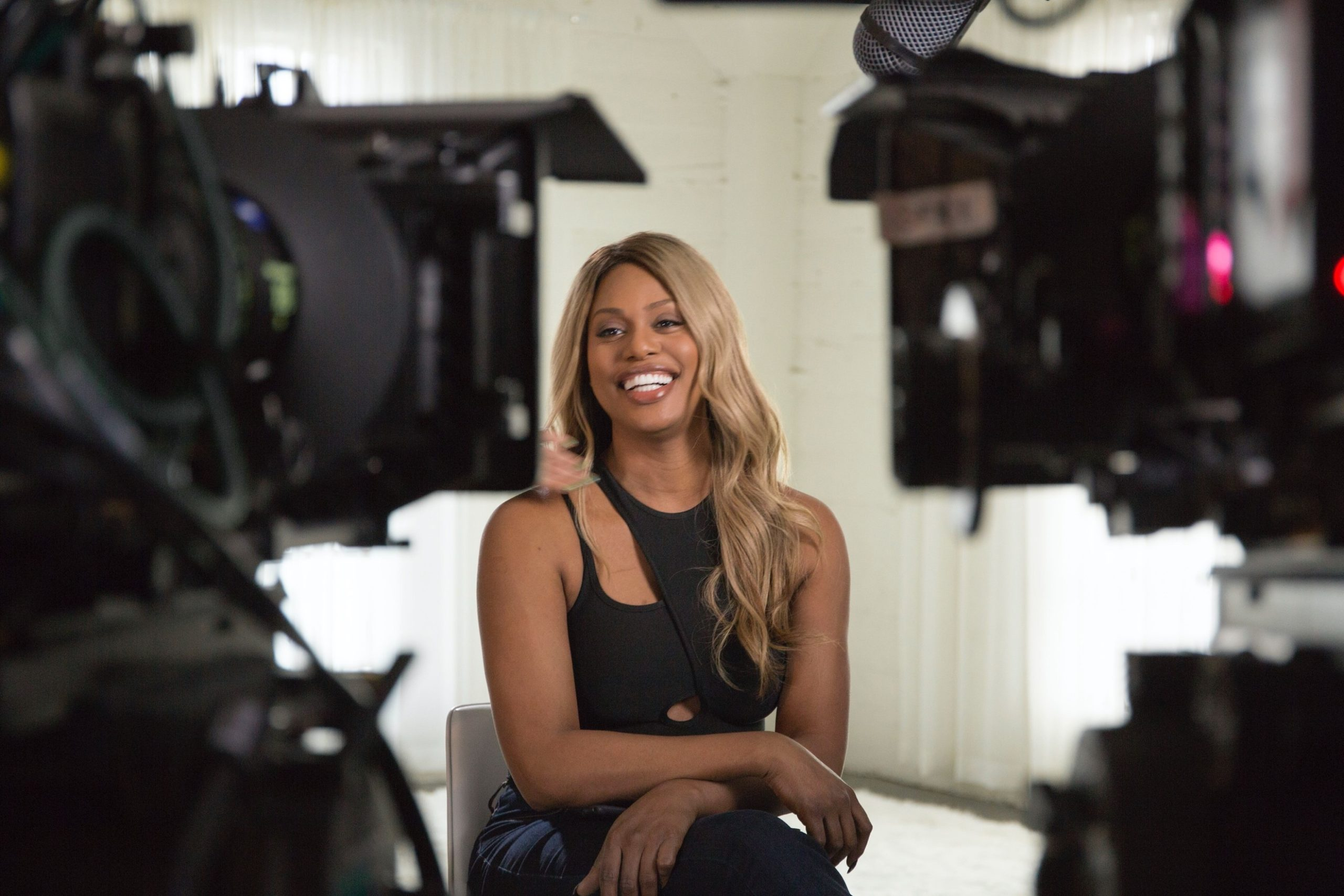 Leverne Cox smiles while sitting between two cameras in the documentary Disclosure: Trans Lives on Screen
