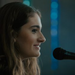 Rachel Sennott faces a microphone in her synagogue in the film Tahara