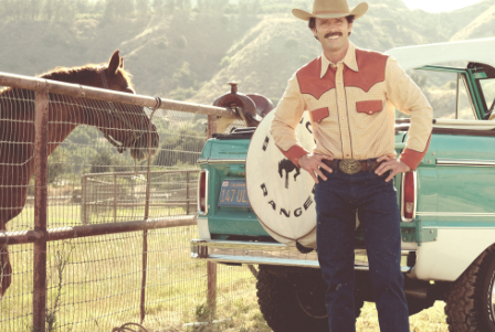 John Bronco (Walton Goggins) standing in pasture by horse