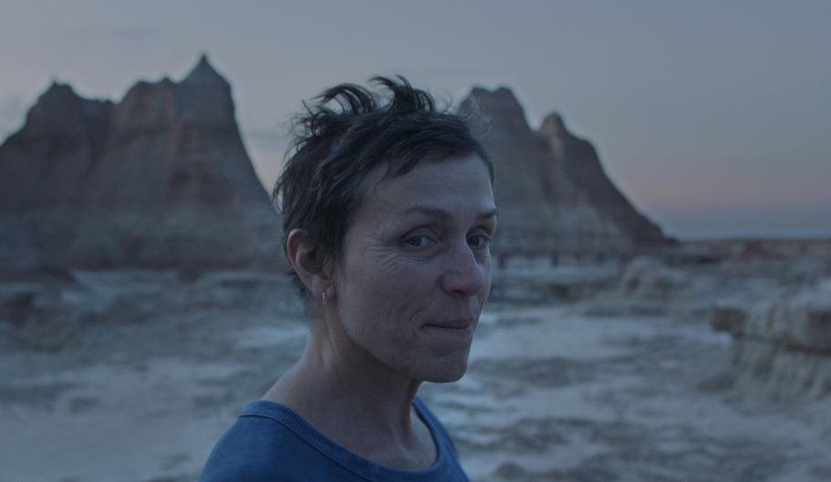 Frances McDormand on a beach staring at camera.