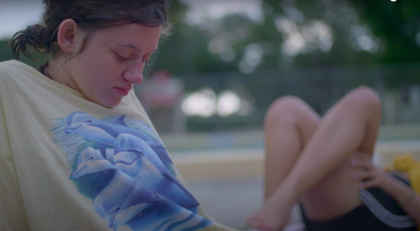 Young girl sits outside, sad.