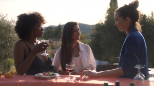 Three women sit outside at a table, drinking wine.