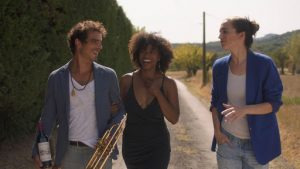 A man and woman, linking arms, walk down a dirt path with a second woman. All three are smiling.