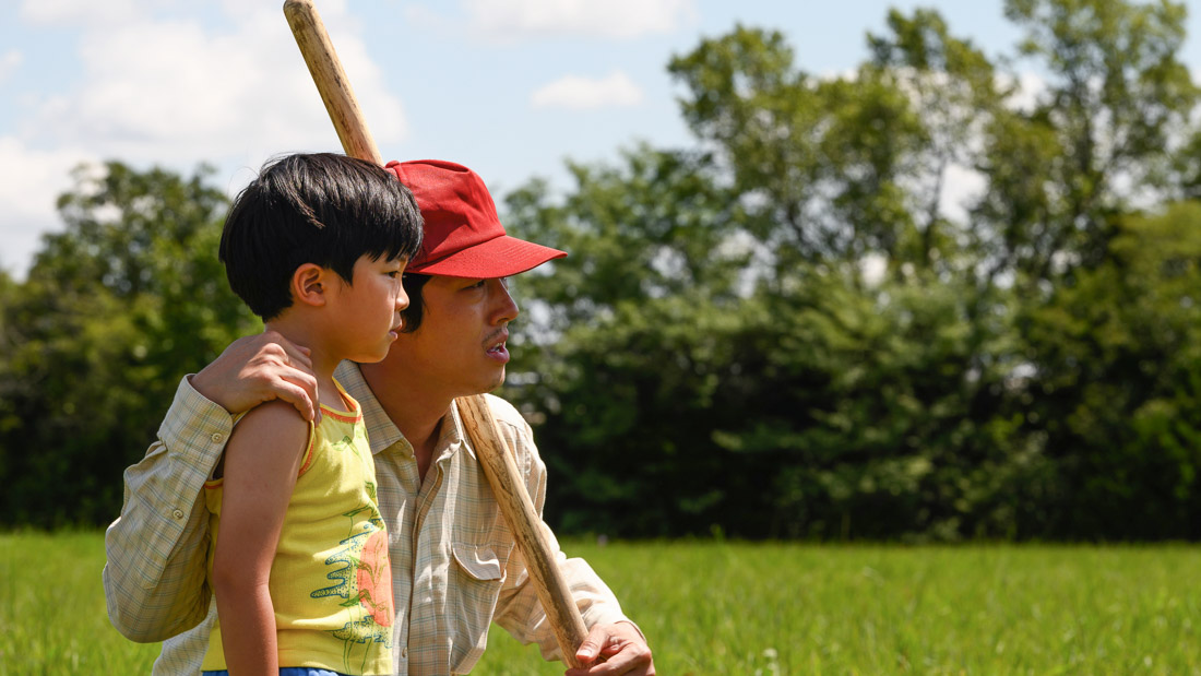 Father and son hold baseball bat.