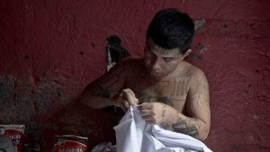 A shirtless man with tattoos sews.