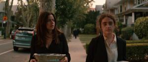 Two young women walk side by side down a sidewalk outside.