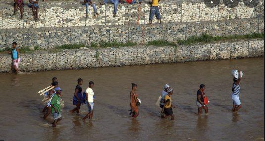 People walking through water near a wall.
