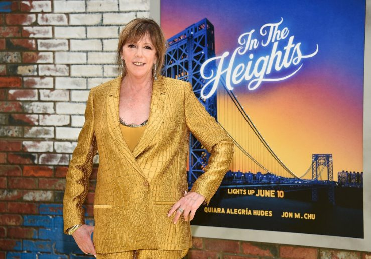 Jane Rosenthal in gold suit in fron of an In the Heights poster.