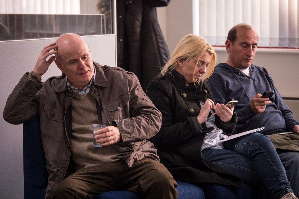 Three people sit in medical waiting room.