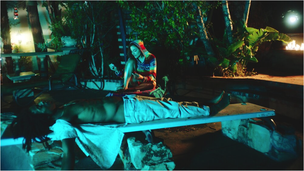 Two people sitting by a pool at night.
