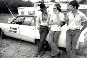 Three men leaning on a police car
