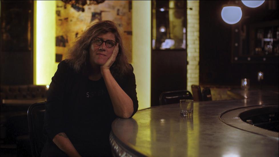 Susan Stryker being interviewed at bar.